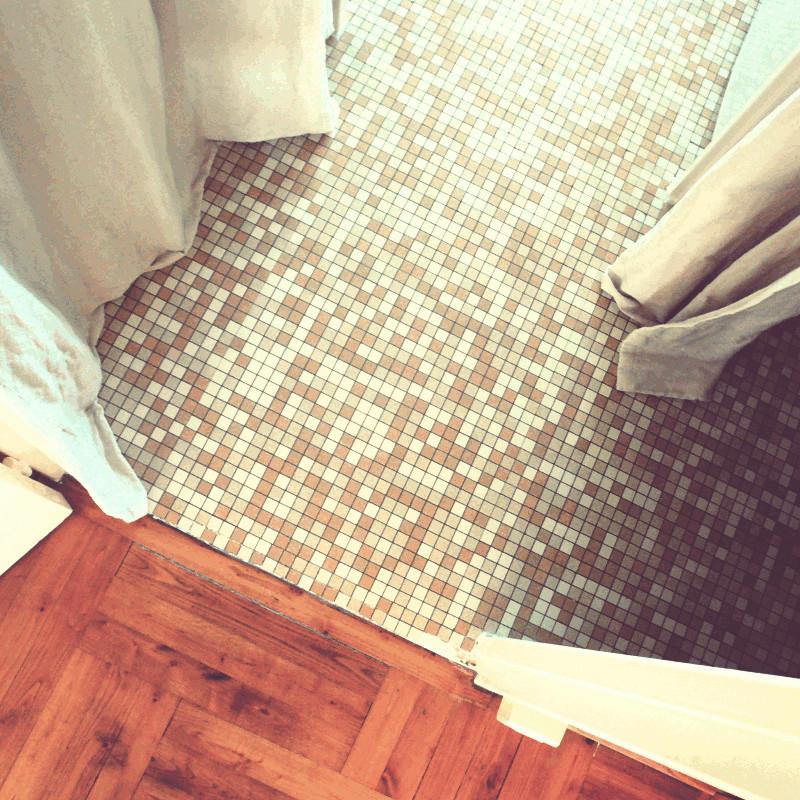 Le sol d'un couloir carrelé d'un camaïeu de beige au croisement de deux portes et d'une paire de rideaux au bord d'un plancher en bois