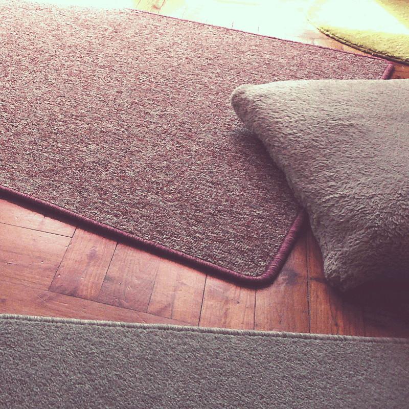 Sur un plancher en bois sont disposés dans tous les sens un tapis rond vert anis, un tapis mauve sur lequel est posé un coussin beige et un tapis gris