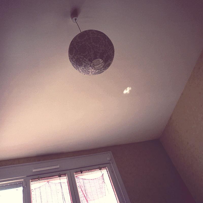 Au plafond où se reflète un pâle rayon de soleil est suspendu un abat-jour en boule de papier crème au motif végétal de couleur brune qui rappelle les stores en bois accrochés à une porte-fenêtre