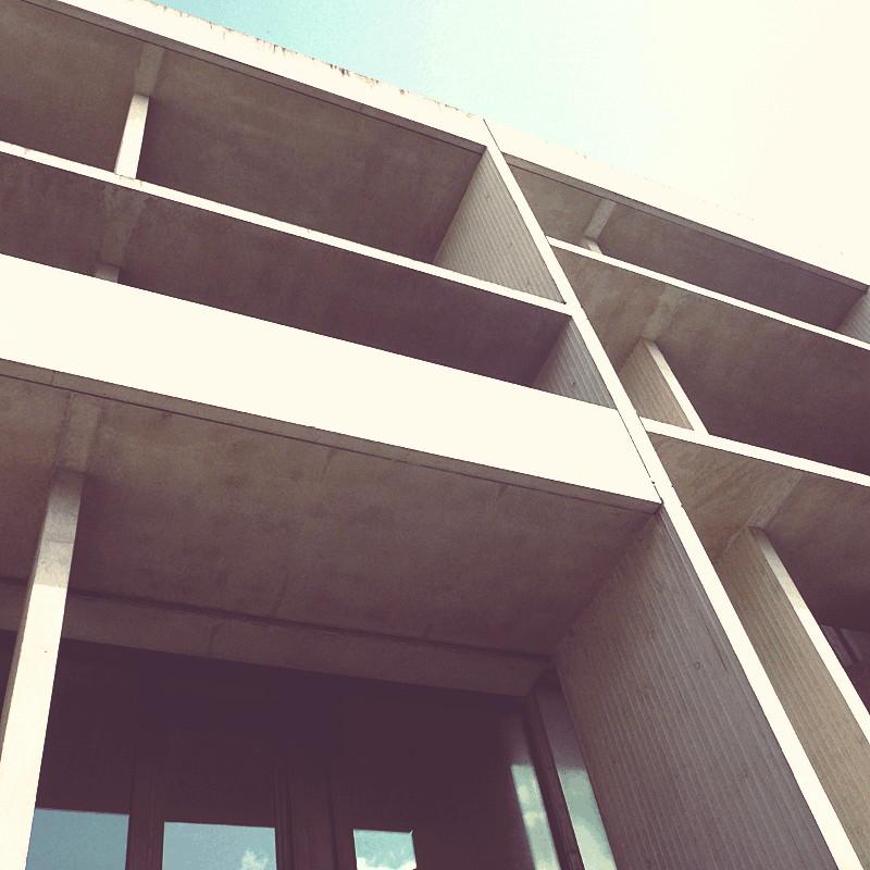 Contre plongée d'une façade de béton où chaque étage est marqué par de larges creux tels des balcons sans garde-fou