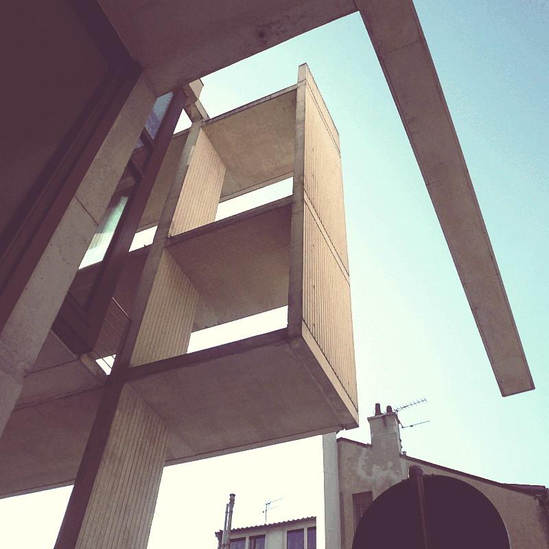 Contre plongée sur un angle du bâtiment où les faux balcons se prolongent dans le vide comme un tiroir sans fond à deux compartiments dressés à la vertical