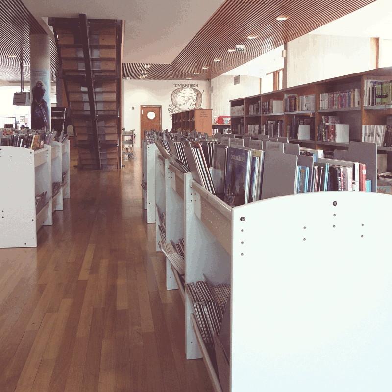 Une bibliothèque au plancher de bois, des rayonnages en chêne d'autres en métal gris clair, entre eux un escalier ajouré en chêne, au fond un mur clair percé d'une porte en chêne pourvue d'un hublot