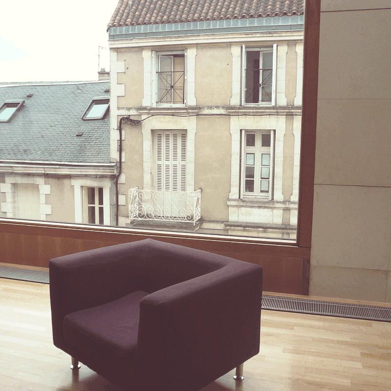 Un fauteuil carré violet sombre sur un plancher de bois clair devant une large baie vitrée encadrée de bois donnant sur des maisons de ville aux murs beiges et volets blancs, l'une avec des tuiles charentaises, un balcon en fer forgé blanc et certaines de ses fenêtres ouvertes, l'autre en toit d'ardoises et lucarnes rectangulaires