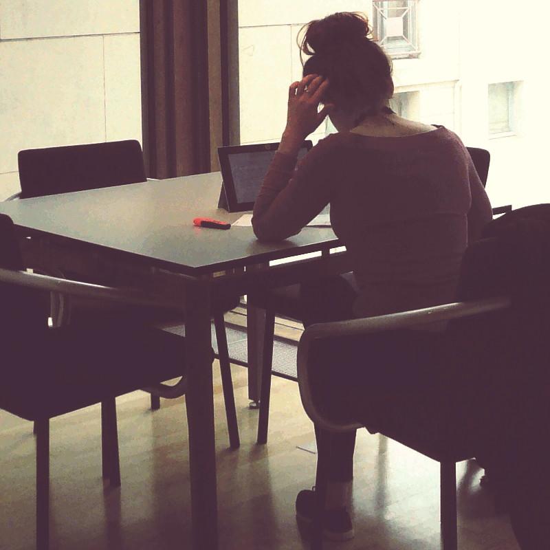 Dans l'ombre d'une baie vitrée exposée au nord, une table carrée entourée de quatre sièges, sur l'un d'entre eux est assise une jeune fille vue de dos habillée d'un pull en laine vieux rose, penchée sur une tablette posée devant elle, les doigts d'une main dans ses cheveux coiffés d'un haut chignon tout rond
