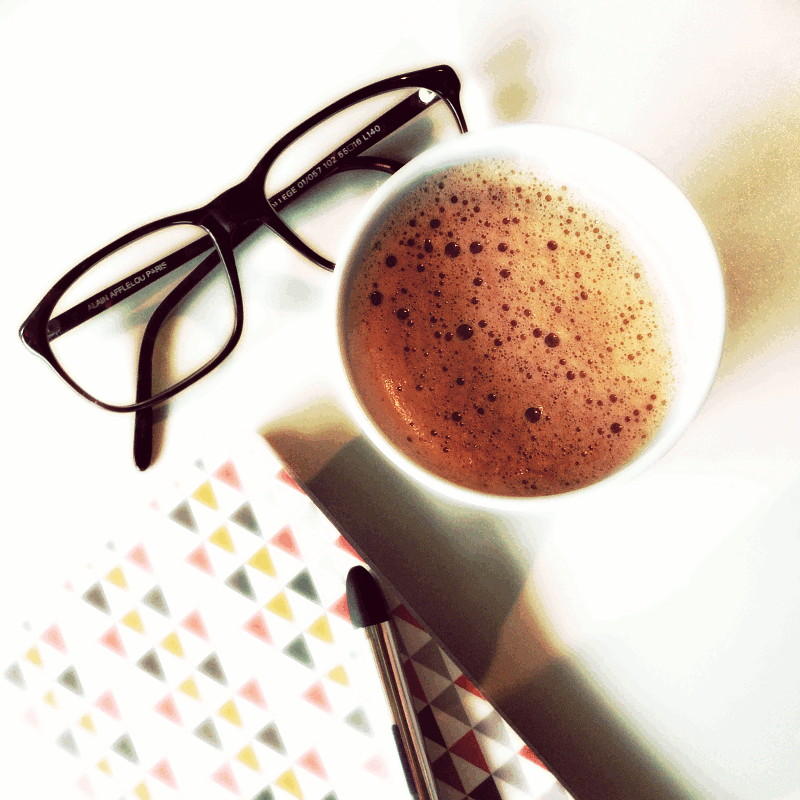 Vue du dessus une paire de lunettes marron foncé, un carnet au motif triangulaire jaune moutarde, anthracite et couleur pêche, un gobelet en carton plein d'un chocolat chaud mousseux