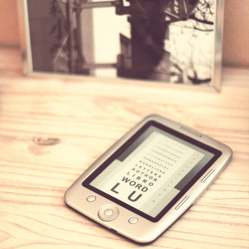 On a whited pine shelf and in front of the frame of a black and white photograph, a digital reader whose screen is in standby