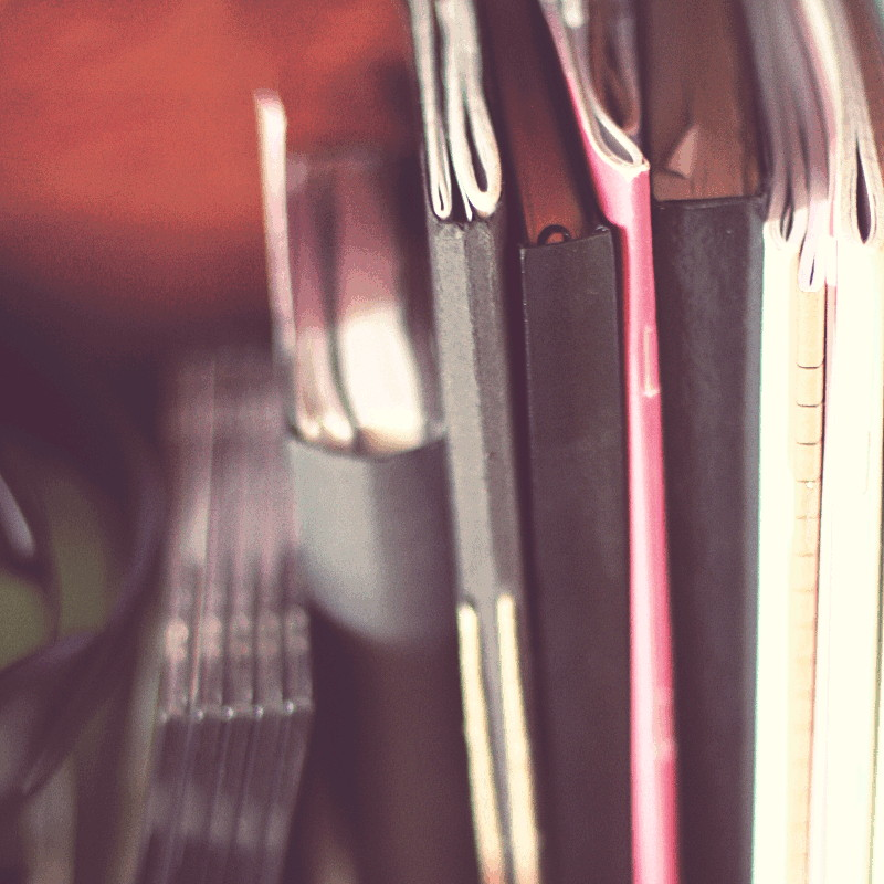 Close-up on a stack of crystal plastic dvds boxes and the slice of notebooks and quires of different formats and covers anthracite, fuchsia pink, white, beige or black
