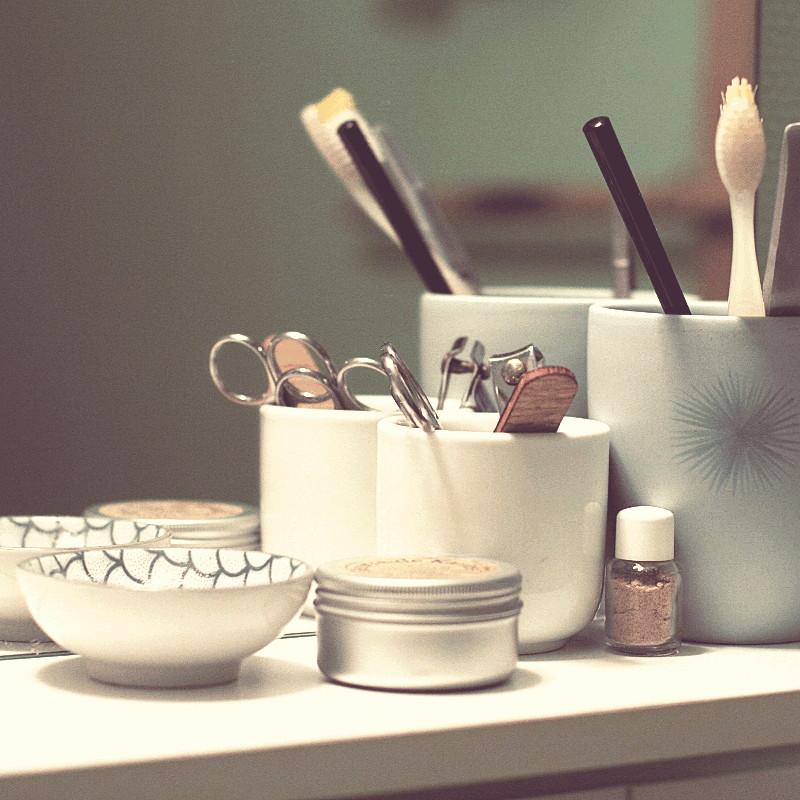Contre le miroir d'une tablette de salle de bain se réflètent deux pots de différentes tailles bleu céladon et blanc où sont rangés brosse à dents, baguette pour chignon et ustensiles de manucure, à côté une coupelle à motif japonais bleu pétrole d'écailles de carpe, une petite boîte ronde en métal blanc, une petite bouteille en verre remplie d'une poudre végétale