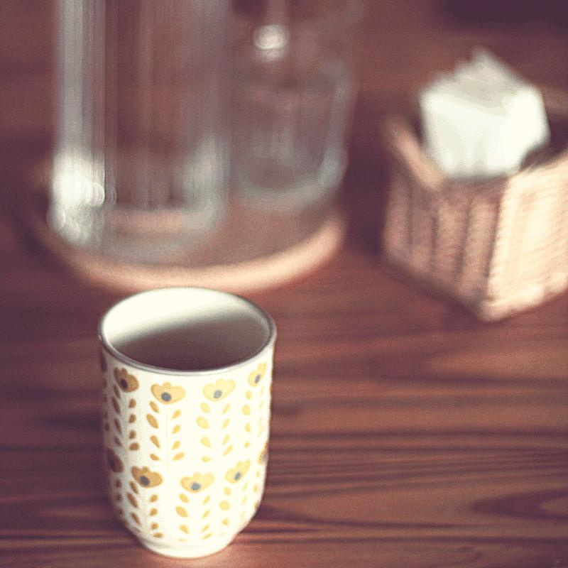 Un mug beige décoré de fleurs ocres devant le flou d'une carafe d'eau, d'un verre et d'un petit panier en osier contenant des mouchoirs en papier