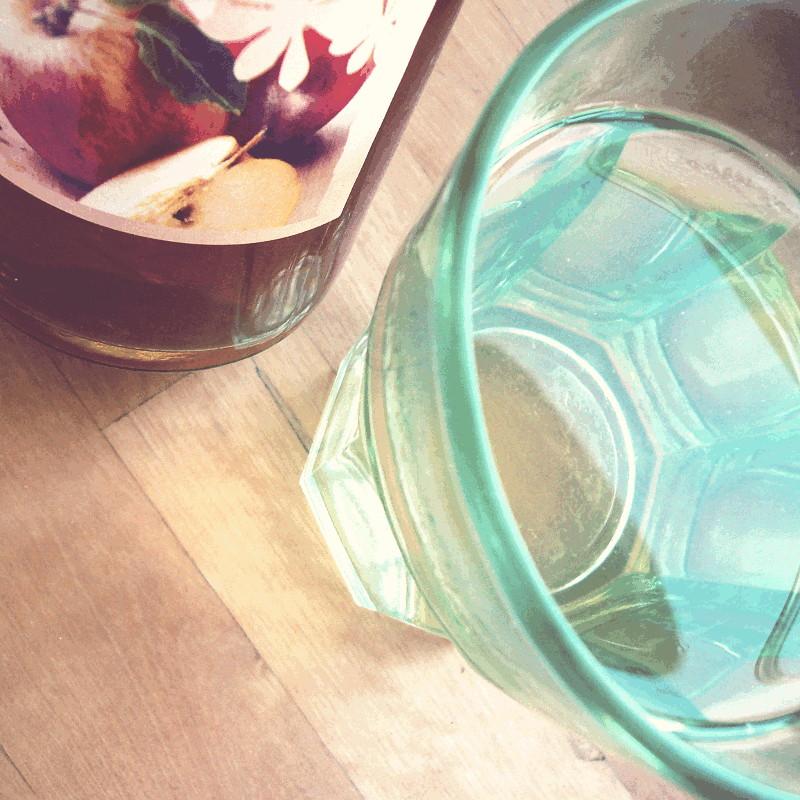 Vue du dessus d'un verre d'eau à côté d'une bouteille de vinaigre à l'étiquette colorée de pommes et de fleurs de pommier