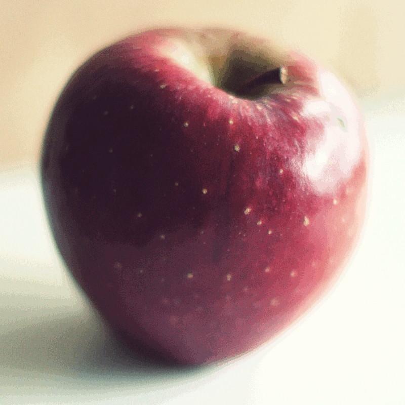 Gros plan sur une belle pomme rouge cerise dont le grain forcé de l'image forme des applats de vert kaki et de gris dégradés