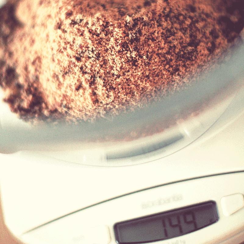 Gros plan sur du sucre complet dans un saladier en verre posé sur une balance et dont l'écran à cristaux liquides indique 149g