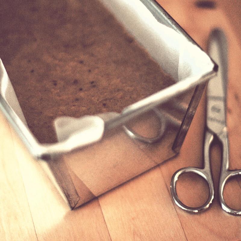 À côté d'une paire de ciseaux en métal, un côté du moule à cake en tôle habillé d'un papier blanc de cuisson rempli d'une pâte mousseuse couleur châraigne