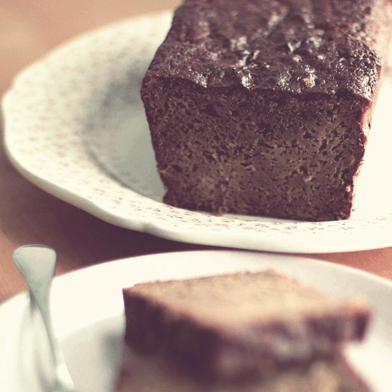 Sur une assiette blanche piquée d'un léger motif rose foncé, un cake brun coupé dévoile une mie dense et fondante