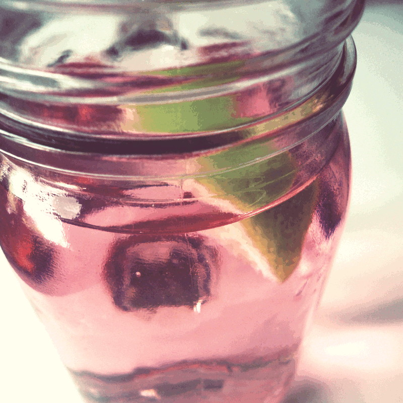 Bocal en verre rempli d'une infusion rose et d'un quartier de citron vert