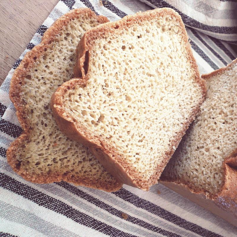 Sur un torchon blanc à rayures grises et noires des tranches de pain maison moulé