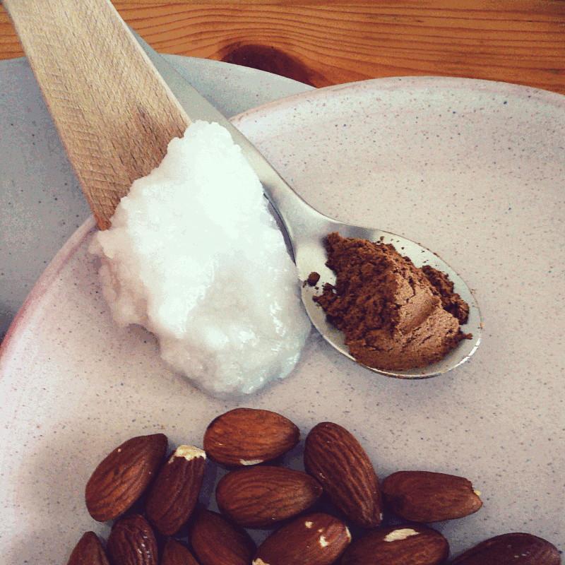 Dans une petite assiette en grès rose clair des amandes et une petite cuillère remplie de poudre de cannelle à coté d'une spatule en bois sur laquelle fond doucement de l'huile de coco figée
