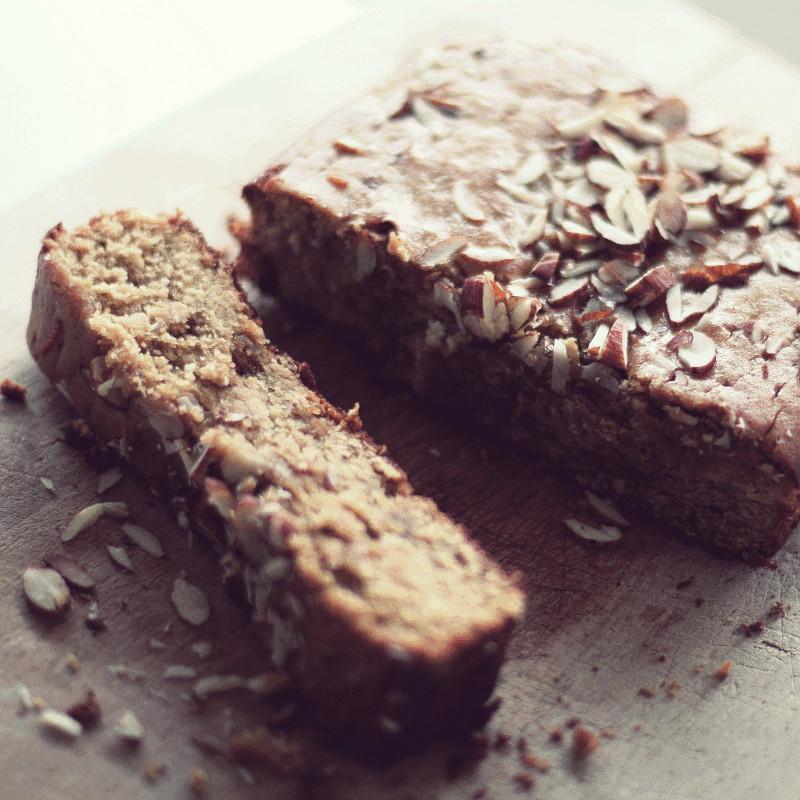 Un large cake brun à la mie fondante et parsemé d'oléagineux émincés