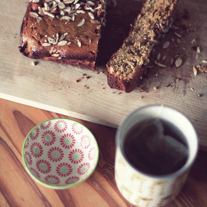 Le même cake posé sur une planche en bois à côté d'un mug où infuse un sachet et une petite soucoupe peinte de fleurs rouges et vertes