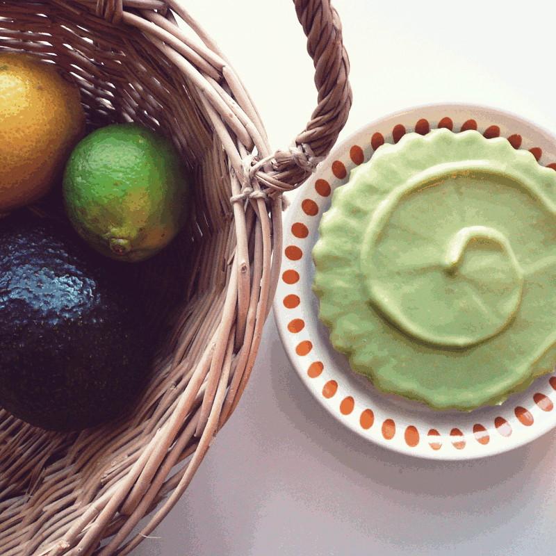 Vue du dessus une tartelette recouverte d'une onctueuse crème vert tendre à côté d'un panier en osier où sont disposés un avocat, une orange et un citron vert