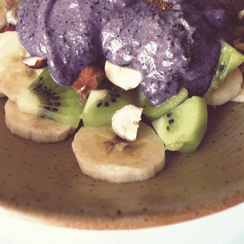 Banane et kiwi coupés sous une couche d'amandes grossièrement concassées et d'une généreuse épaisseur de mousse violette au lait de coco et mûres