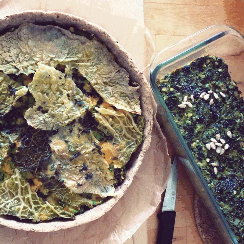 Vus du dessus une tarte rustique au chou vert sur son papier de cuisson à côté d'un moule à cake en verre dans lequel a cuit une terrine d'épinards aux graines de tournesol