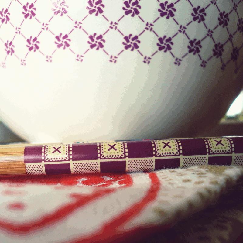 Gros plan sur les motifs violets et géométriques d'un bol et d'une baguette japonaise en bois le tout posé sur une serviette orange et brun