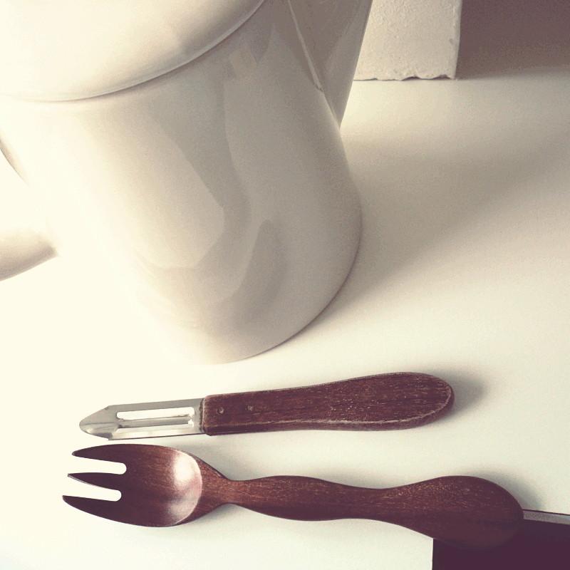 Une fourchette en bois et un économe posés sur ce que l'on devine être un coin de tablette et un mur blancs tout près d'une théière