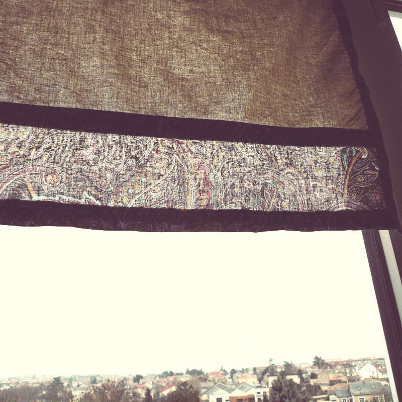 La vue sur des toits de maisons au loin en dessous d'un store en tissu couleur sable avec une bande cousue dans le bas d'un motif floral assorti