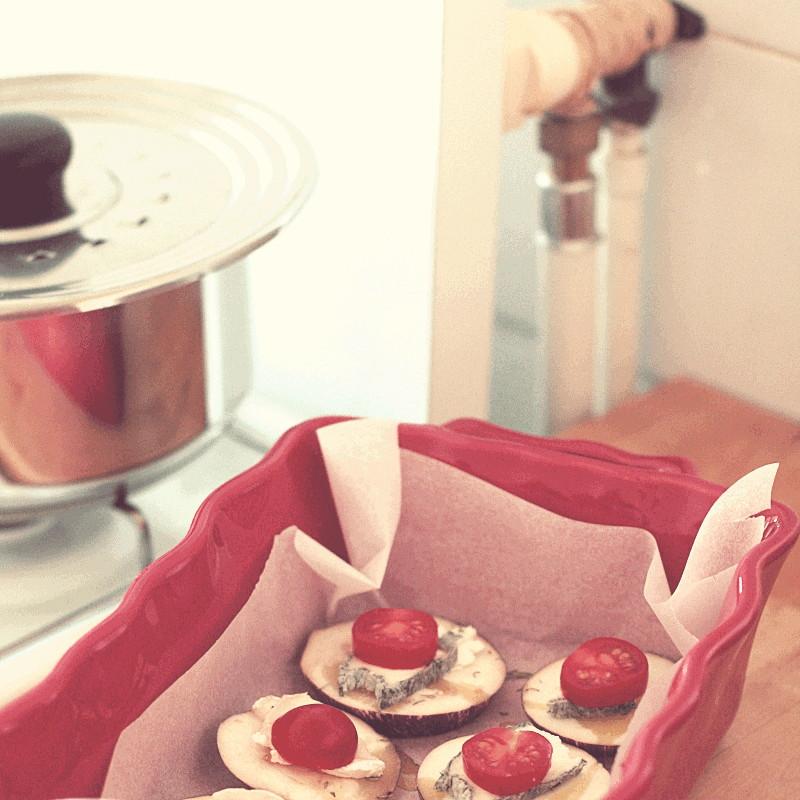 Un bout de casserole en inox posée sur une gazinière à côté d'une partie d'un plan de travail en bois et d'un plat émaillé de rouge où sont disposées des tranches d'aubergine recouvertes de fromage de chèvre et d'une tomate cerise sur une feuille de papier de cuisson