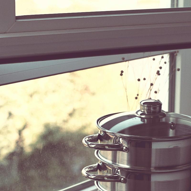 Une portion de fenêtre en pvc blanc, rangé devant la vue floue mais végétale, un cuit vapeur en inox
