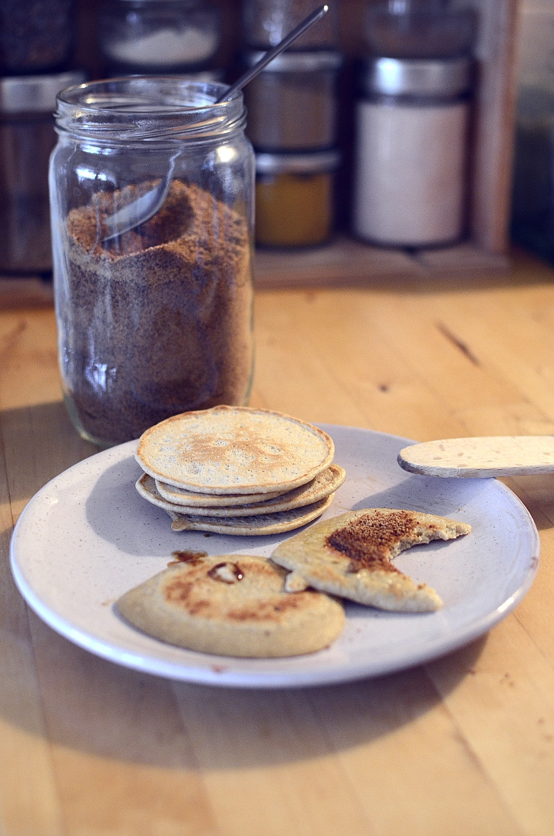 A wooden worktop, in the blurred background a recycled wooden box is full of jars of spices, in front of it a blue glass jar filled with coconut sugar, a pale pink plate in sandstone in which a stack of small golden pancakes are placed next to two other sprinkled of coconut sugar