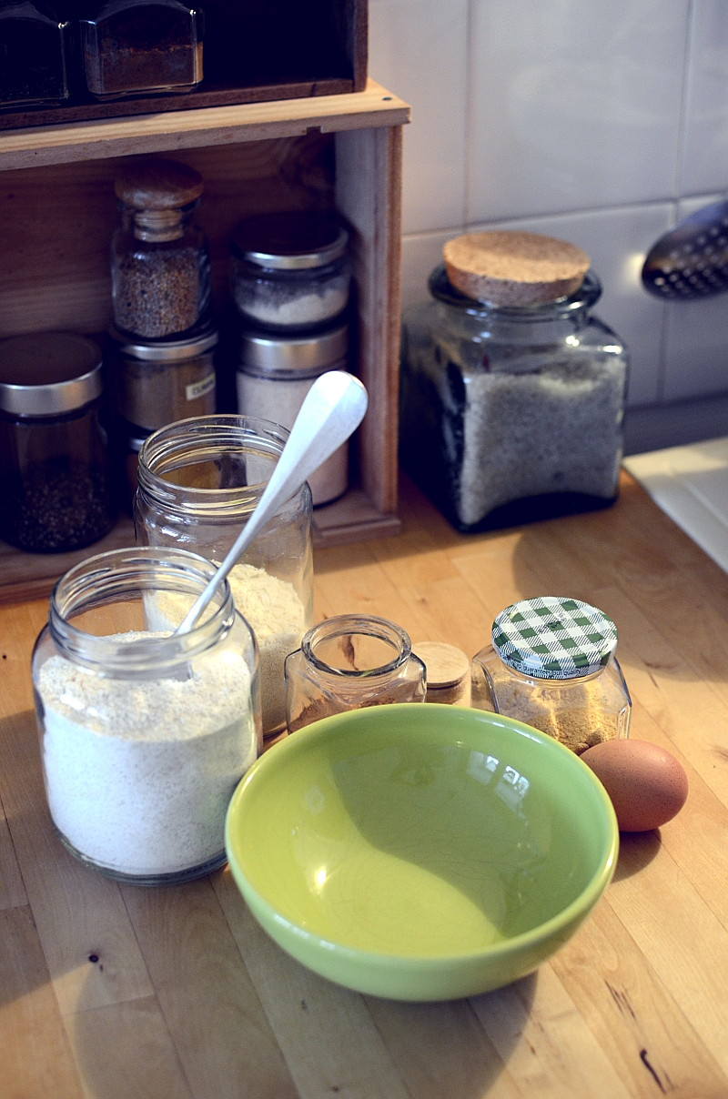 On the pine worktop, in front of the spice box and a large glass jar of coarse salt, a green anise bowl with a flat bottom and the jars of all the ingredients for the recipe