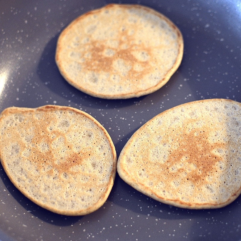 Three pancacakes are cooking in a pan