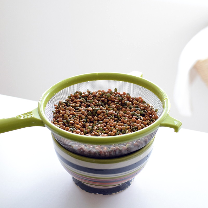 In a green colander over a striped bowl, a mixture of green and pink lentils are draining