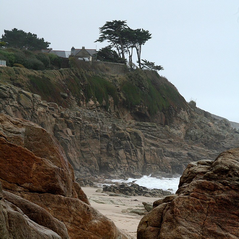 Une falaise au bord de l'océan dans le creux d'une plage par temps de pluie arbore un granit caramel que couronne un manteau de verdure sous une plantée de pins maritimes où l'on devine les ardoises d'un manoir breton