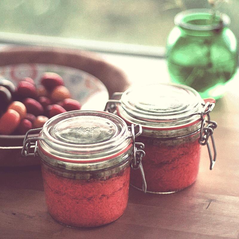 Près d'une fenêtre, d'une corbeille de fruits et d'un vase en verre vert, deux bocaux de carottes lactofermentées