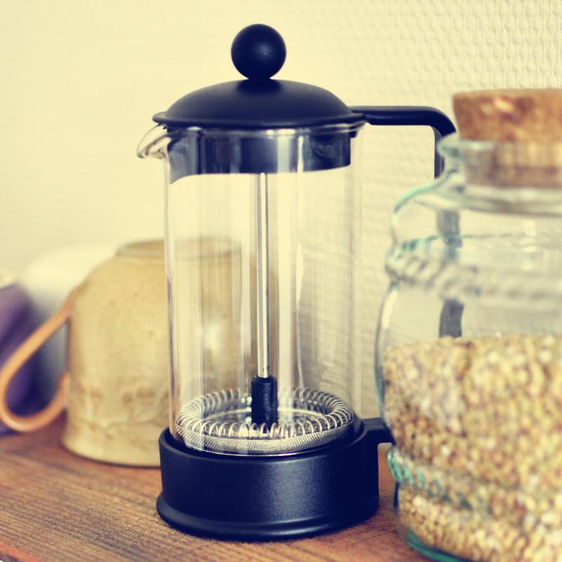 Sur la boîte en bois, entre une tasse en grès et un bocal rempli de graines de sarrasin, une cafetière individuelle en verre à piston