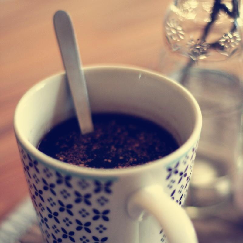 Gros plan sur un mug à motif violet rempli de café à côté d'une petite bouteille en verre avec de petites fleurs en relief