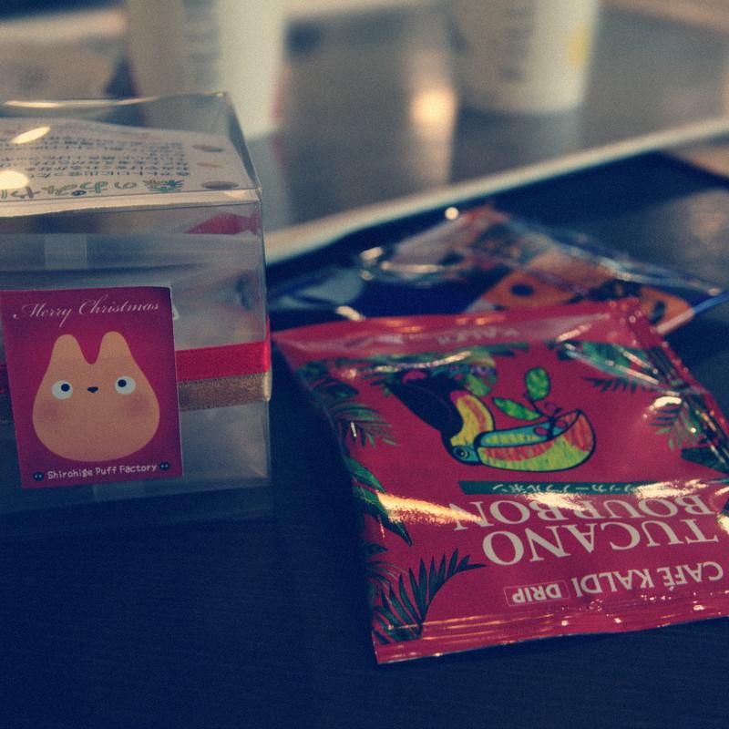 Devant un plateau où sont posés deux gobelets en carton, une boîte carrée en plastique transparent avec un Totoro dessiné sur l'étiquette, à côté des sachets en papier alus de couleurs vives