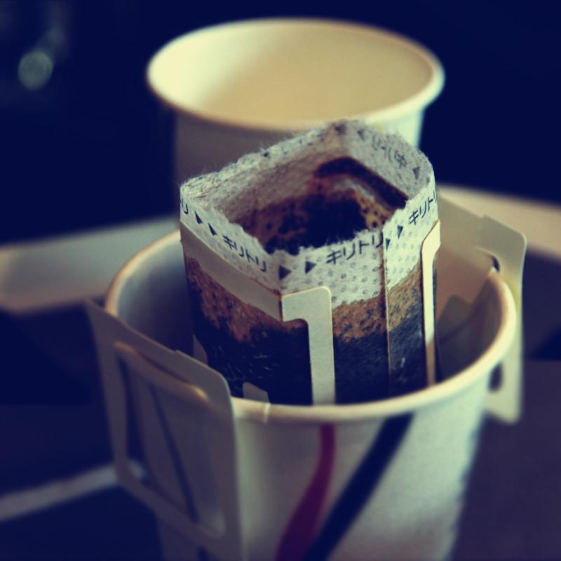 Dans un gobelet en carton, un filtre tubulaire rempli de café en train d'infuser tient par deux poignées en carton insérés sur chaque côté du gobelet