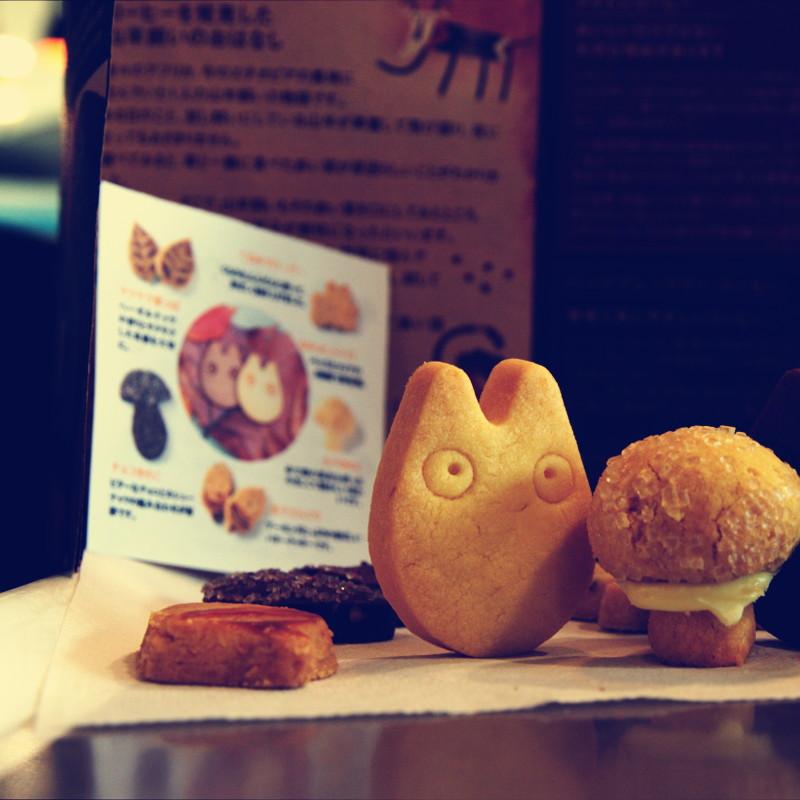 Devant des papiers illustrés de présentation, des biscuits sablés en forme de Totoro, de champignons ou de feuilles posés sur une serviette en papier