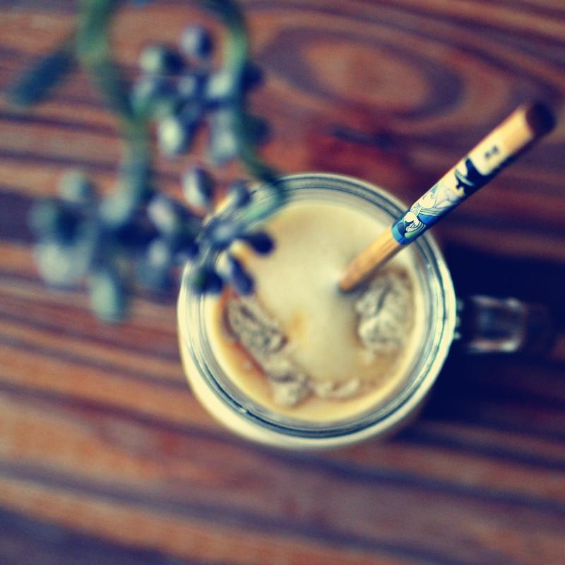 Vu de dessus le mug en verre rempli de smoothie sous une branche de fleurs violettes en bourgeons, mise au point seulement sur la baguette en bois et le personnage japonais qui la décore
