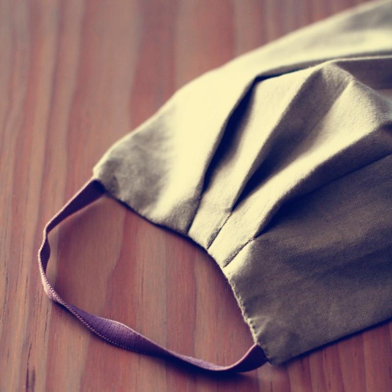 Détail de la couture d'un masque en tissu beige et élastique rose à trois plus