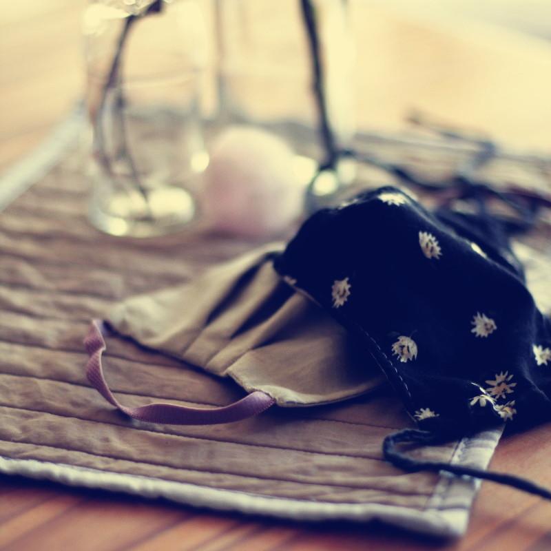 Les deux masques posés sur un set de table en tissu beige et gris clair devant des vases en verre et un morceau de quartz rose brut que l'on devine dans le flou