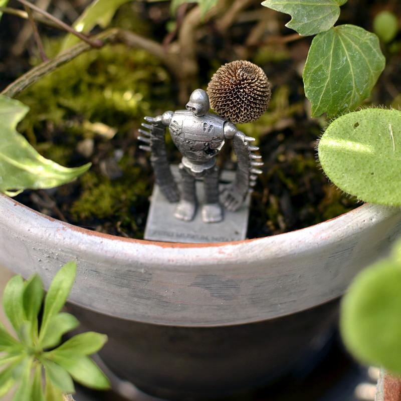 Une petite figurine en métal du soldat robot du Château dans le Ciel de Miyazaki, entourée de mousse, est plantée dans un pot comme se tenant au bord d'un balcon
