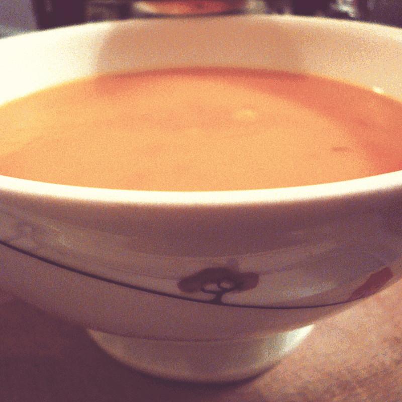Gros plan sur un bol décoré d'un petit arbre et rempli de soupe au potimarron