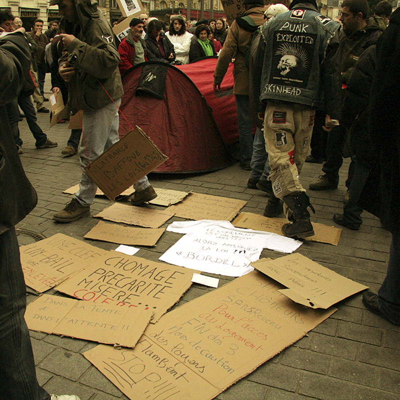 Some cardboard signs of claims laid on the ground in the middle of a crowd