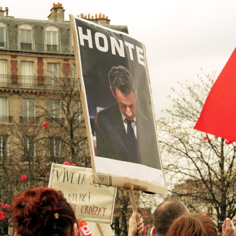 A sign brandished in the crowd shows the face of French President Sarkozy under the word
