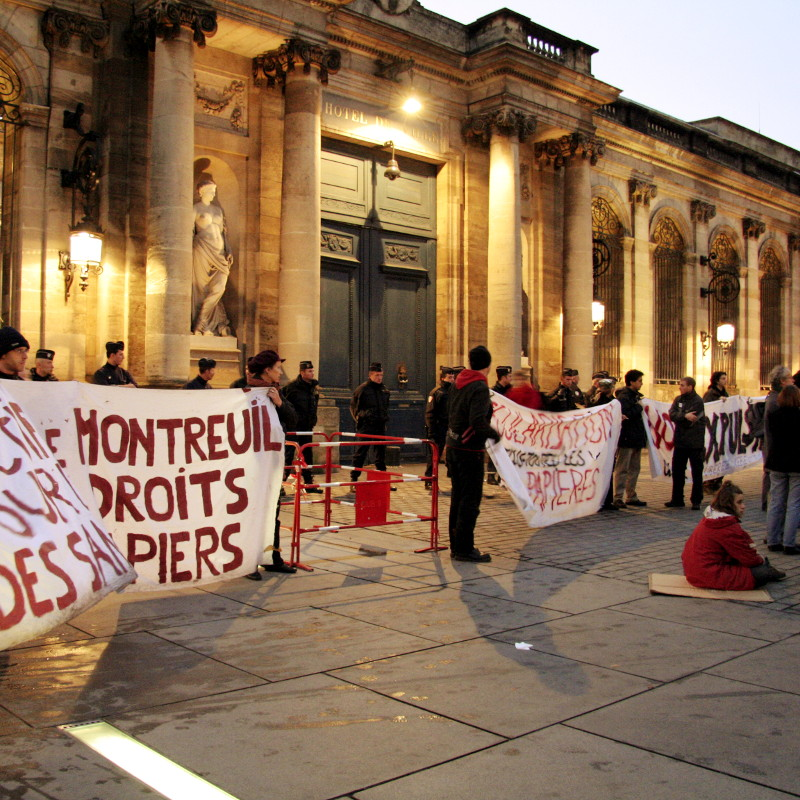 <In front of the town hall in bordeaux, people in line are holding large white banners covered with red inscriptions for the rights of undocumented migrants.